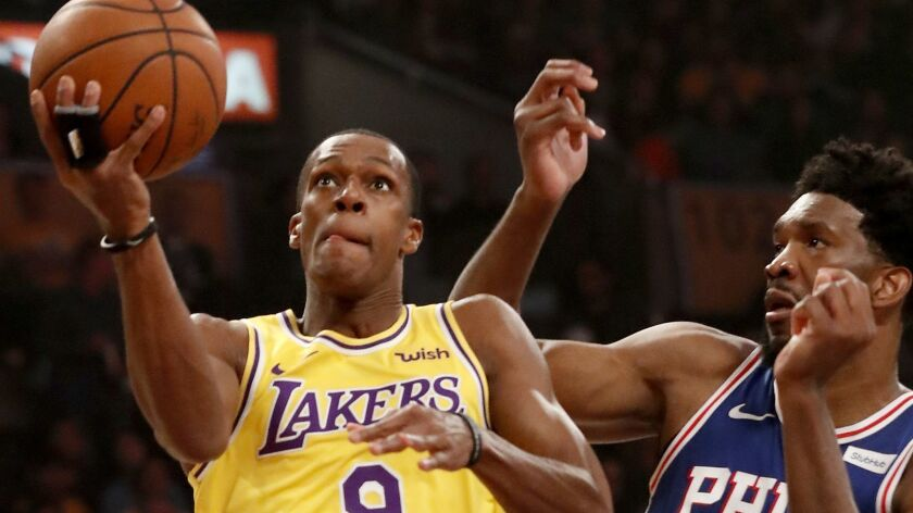 LOS ANGELES, CALIF. - JAN. 29, 2019. Lakers guard Rajon Rondo drives to the basket against Sixers f