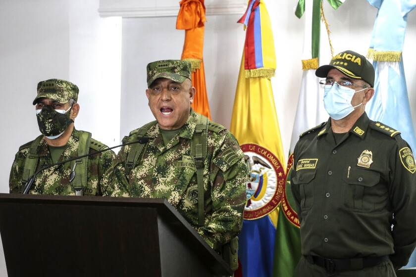 Three military officers in uniform at a news conference