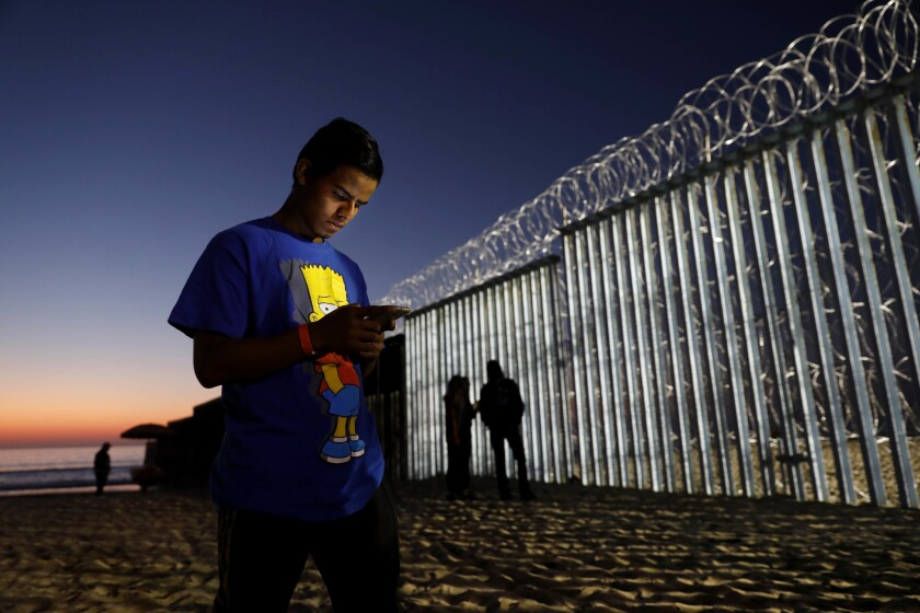Honduran Jorge Sevilla, 20,checks his phone at Playas Tijuana along the U.S. - Mexico border in Tijuana. Sevilla is not sure if he will seek political asylum or cross illegally into San Diego.
