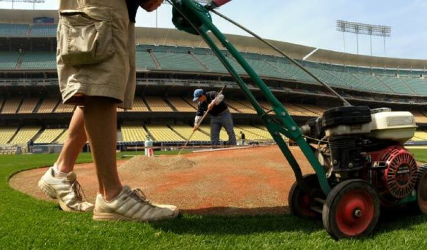 Staff workers get the field ready before an opening day game at Dodger Stadium.
