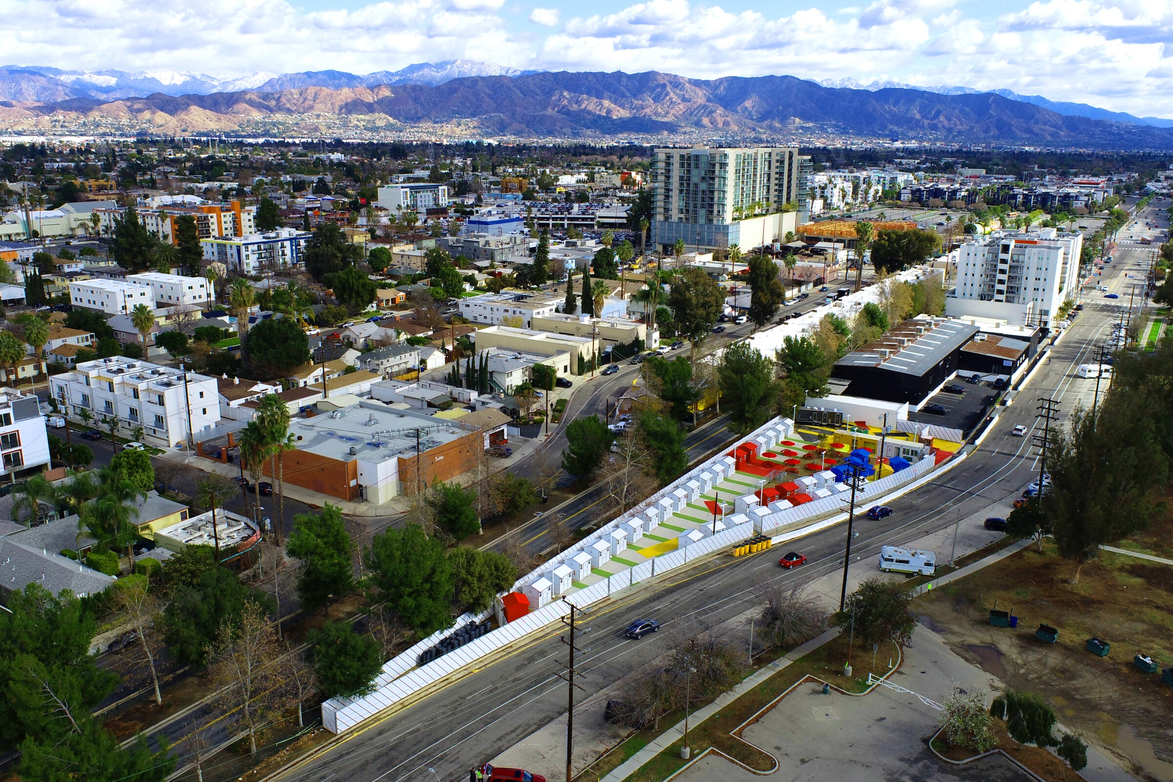 An aerial view shows tiny homes in shades of white, red, blue and yellow tucked into a narrow triangle of land