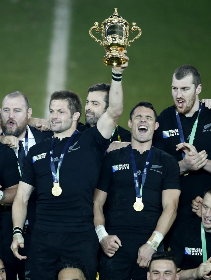 New Zealand All Blacks captain Richie McCaw holds the Webb Ellis trophy aloft as his teammate Dan Carter celebrate's after their Rugby World Cup final win over Australia at Twickenham Stadium, London, Saturday, Oct. 31, 2015.  (AP Photo/Alastair Grant)