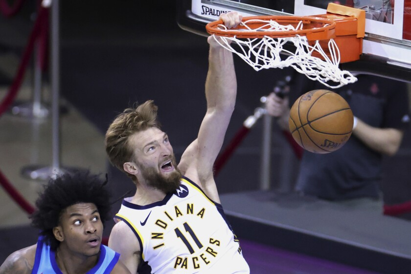 Indiana Pacers' Domantas Sabonis dunks against Houston Rockets' Kevin Porter Jr. during the fourth quarter of an NBA basketball game Wednesday, April 14, 2021, in Houston. (Carmen Mandato/Pool Photo via AP)