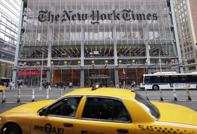 The New York Times building in New York in 2019, with people walking in front of it and a taxi in the foreground.