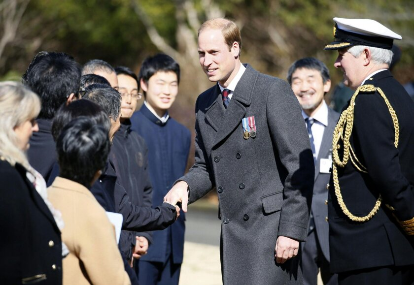 Britain's Prince William, center, talks people during his visit at Yokohama War Cemetery in Yokohama, near Tokyo Friday, Feb. 27, 2015. William is on his first visit to Japan. (AP Photo/Kyodo News) JAPAN OUT, MANDATORY CREDIT