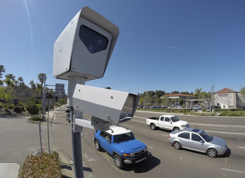 In this 2014 file photo, cars drive past a red-light camera at the intersection of South Melrose Drive and Hacienda Drive in Vista.