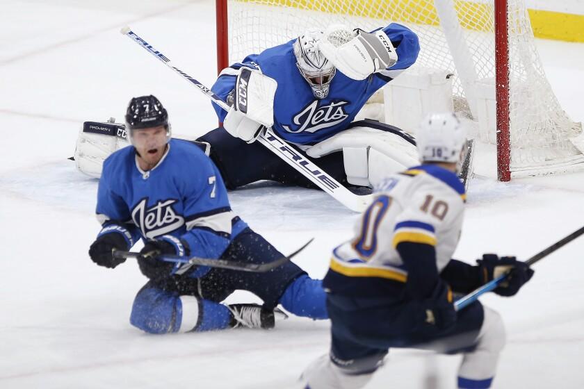 St. Louis Blues' Brayden Schenn (10) scores against Winnipeg Jets goaltender Connor Hellebuyck (37) as Dmitry Kulikov (7) defends during the third period of an NHL hockey game Saturday, Feb. 1, 2020, in Winnipeg, Manitoba. (John Woods/The Canadian Press via AP)