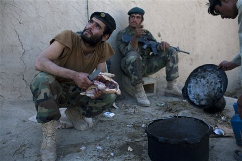 Afghan soldiers attached to Bravo Company 2-502 Infantry Regiment, 101st Airborne Division, prepare lunch at an outpost near Forward Operation Base Howz-e-Madad, Zhari district, Kandahar province, Afghanistan, Wednesday, Oct. 6, 2010. (AP Photo/Rodrigo Abd)