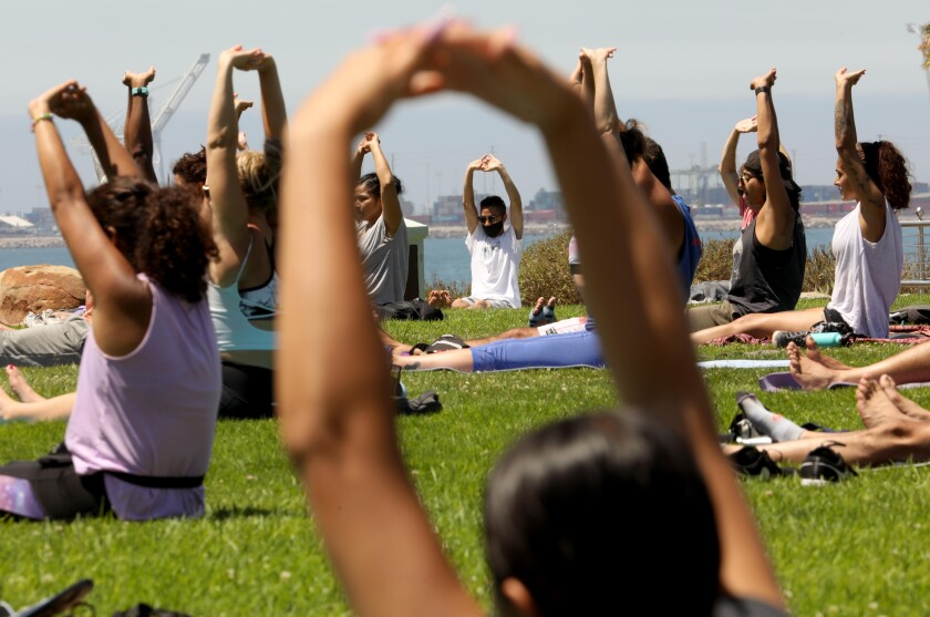 """People participate in a session of, """"Yoga on the Bluff,"""" provided by Yogalution Movement along Ocean Blvd. on Sunday."""