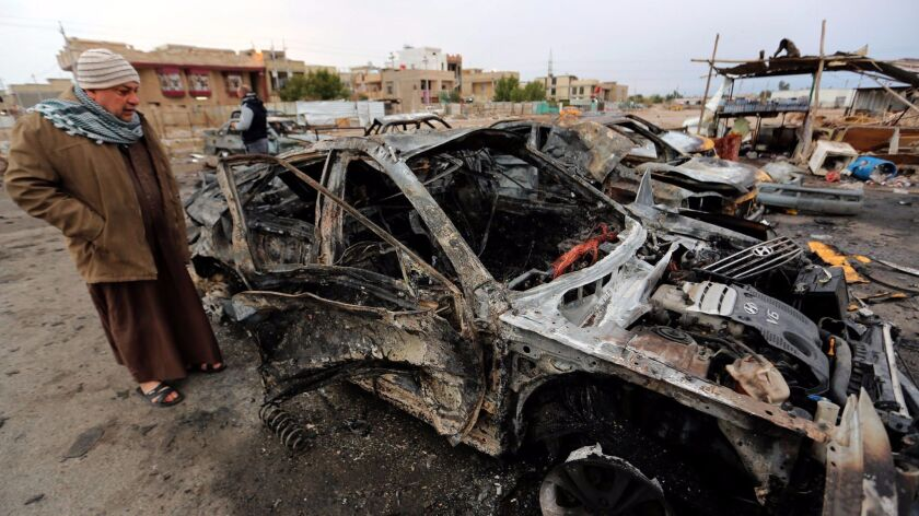 A man stands amid the wreckage after a car bomb attack in Baghdad on Feb. 16.