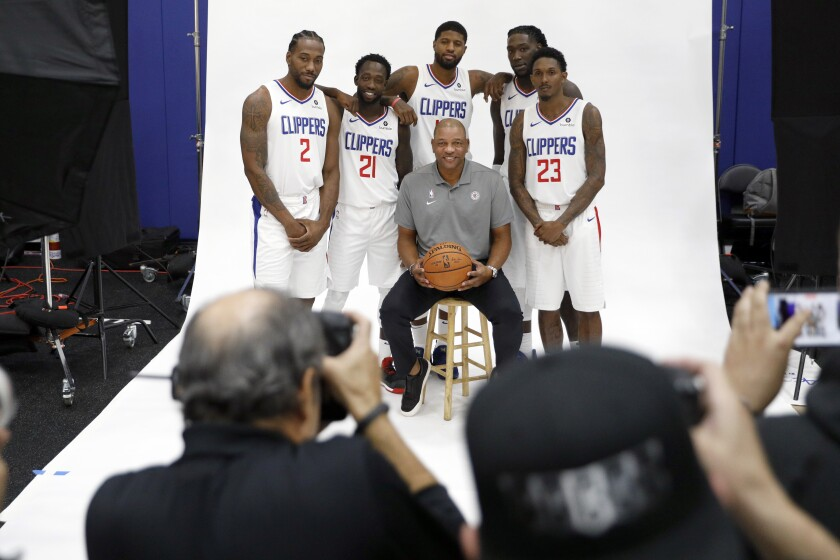 Clippers players (from left) Kawhi Leonard, Patrick Beverley, Paul George, Montrezl Harrell and Lou Williams pose for photos with coach Doc Rivers during media day Sunday.