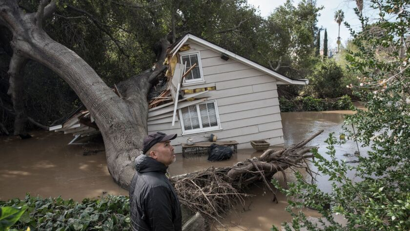 Rob Souza surveys damage to a cottage on his property just west of Coyote Creek, where floodwaters breached his sandbag wall and an oak tree collapsed.