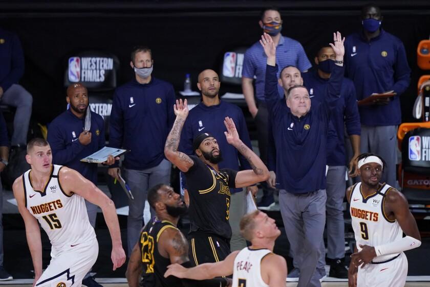 Anthony Davis (3) de los Lakers de Los Ángeles observa tras disparar un triple en medio de Nikola Jokic