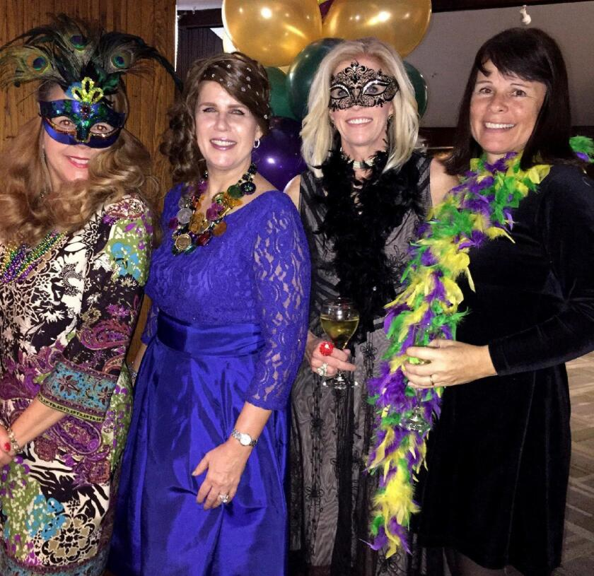 Jill Weinlein, from left, La Cañada Junior Women's Club President Brenda Gant, Marikay Cuthill and Tracey Nelson are in a Mardi Gras mood at the organization's fundraising party.