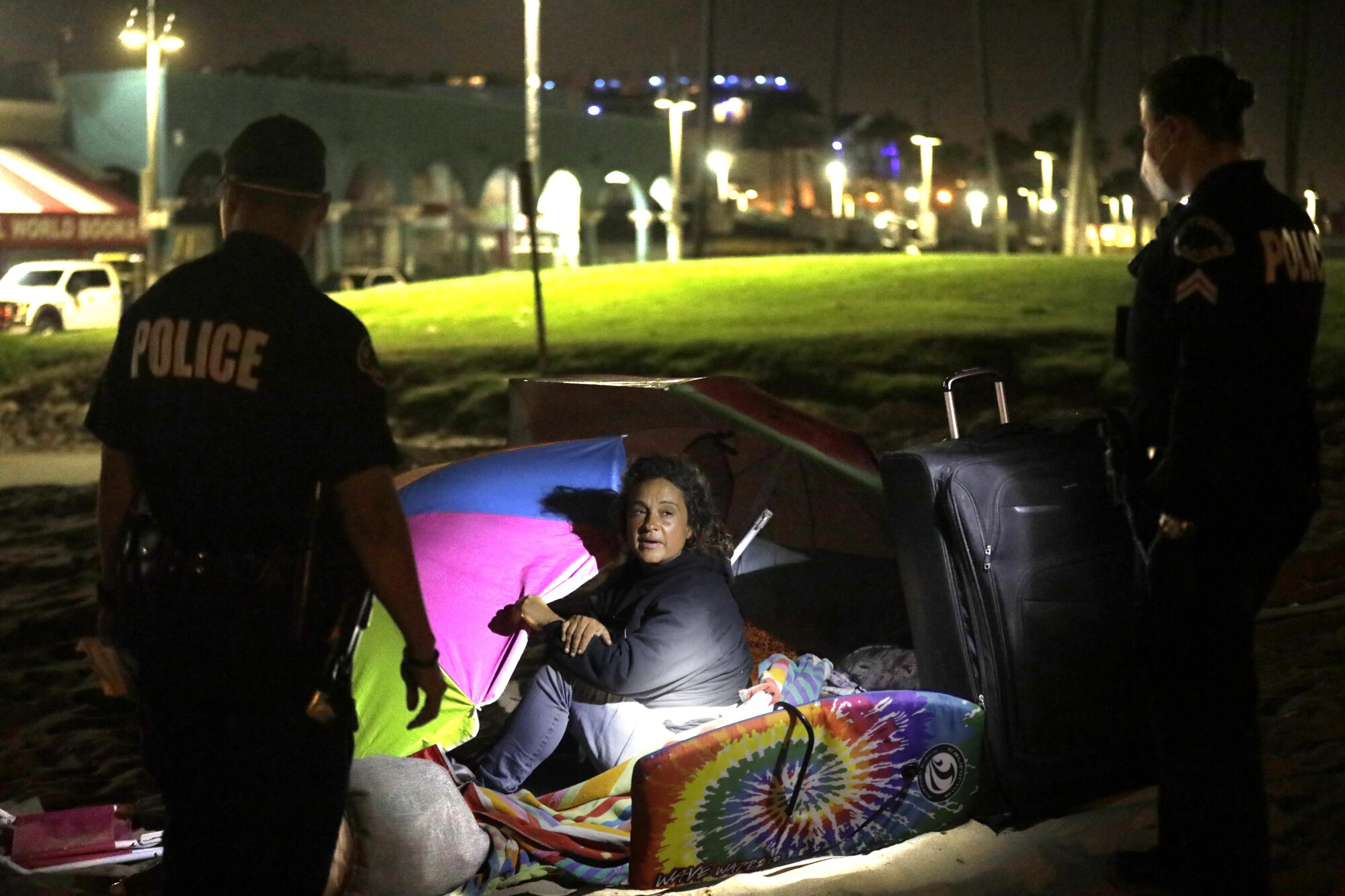 LAPD officers talk to a homeless woman camping along the boardwalk in Venice.