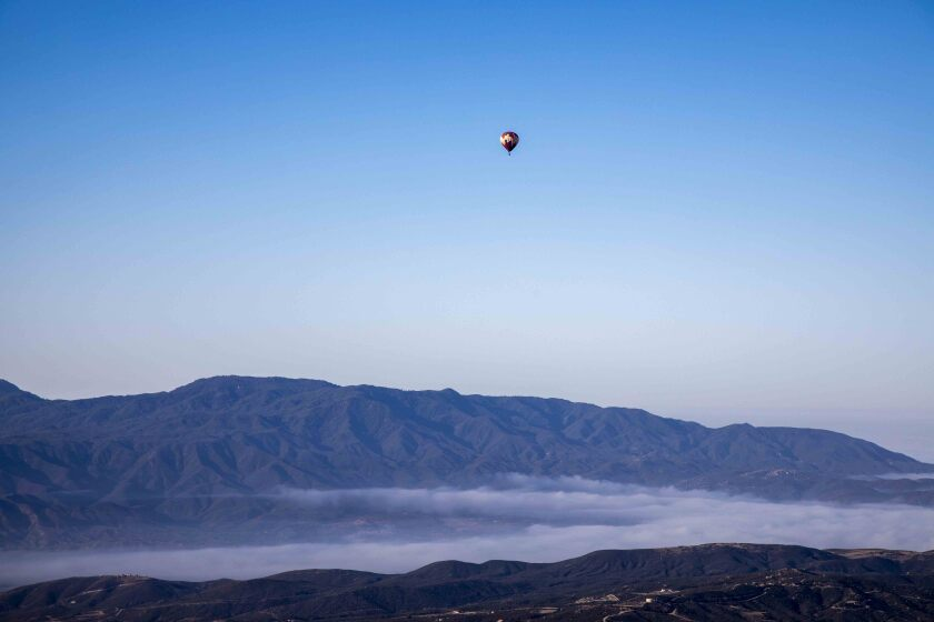 A hot air balloon is seen in the distance over rugged mountains and low fog.