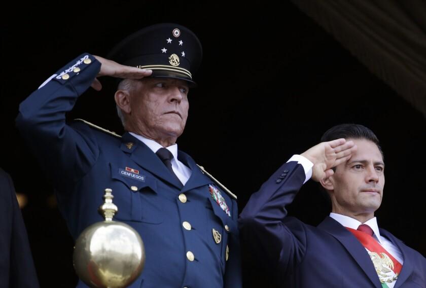 Defense Secretary Gen. Salvador Cienfuegos and Mexico's President Enrique Pena Nieto salute during a military parade
