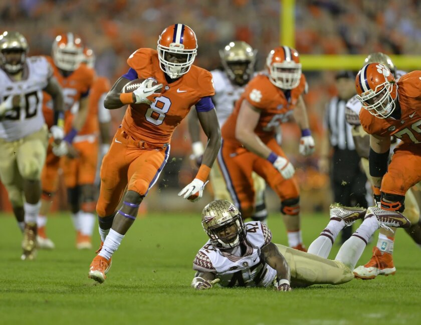 Clemson's Deon Cain (8) rushes out of the tackle attempt by Florida State's Lamarcus Brutus on his way to a touchdown during the second half of an NCAA college football game Saturday, Nov. 7, 2015,  in Clemson,  S.C.  Clemson won 23-13. (AP Photo/Richard Shiro)