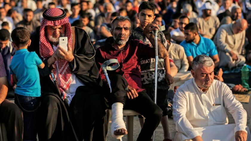 Worshipers and protesters attended morning prayers marking Eid al-Fitr at the Israel-Gaza border east of Gaza City on June 15, 2018.