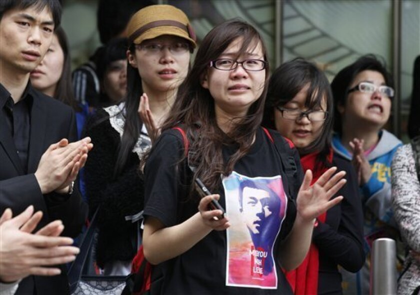 A tearful fan, center, along with others sings a song of the late Hong Kong actor-singer Leslie Cheung outside a hotel where Cheung jumped to his death, in Hong Kong Monday, April 1, 2013. Cheung's fans placed flowers to mark the 10th anniversary of the death of Hong Kong screen and singing legend