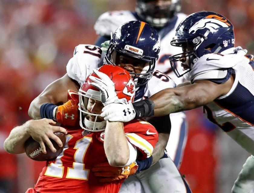 Los jugadores de los Denver Broncos Todd Davis (C, detrás) y Corey Nelson (d), durante un partido. EFE/Archivo