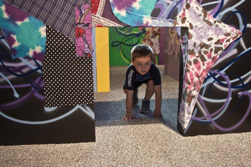 A young visitor investigates Shinique Smith's maze, decorated with used clothing. Maurice Hewitt