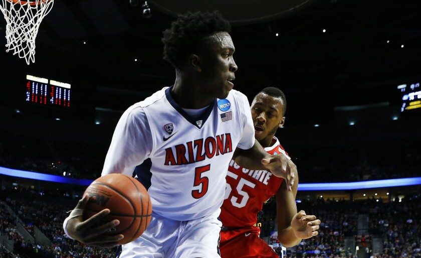 Arizona forward Stanley Johnson controls the ball against Ohio State center Trey McDonald during the first half of the Wildcats' 73-58 victory over the Buckeyes in a third round game of the NCAA tournament.