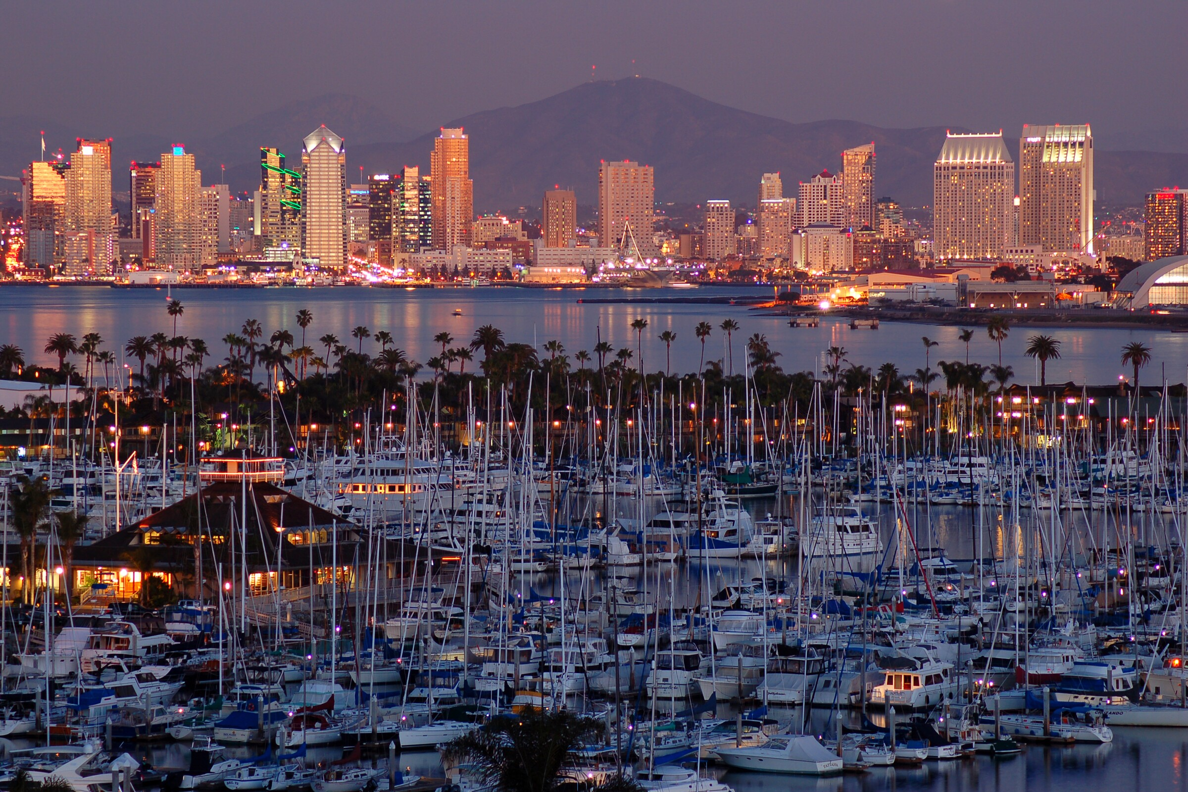 The sunset is reflected in the skyline and the calm marina of San Diego, California.