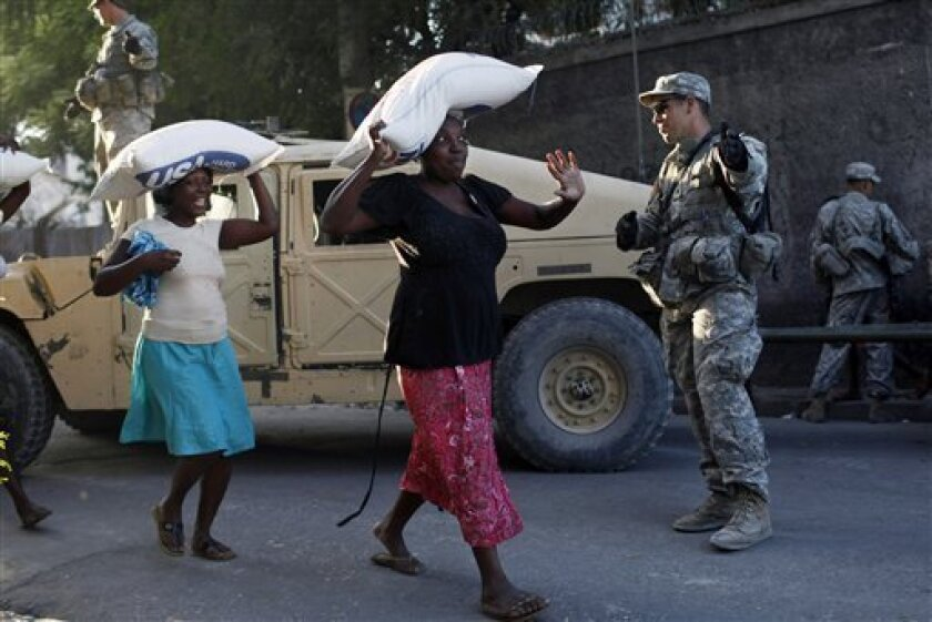 Women carry sacks containing rice during a food distribution watched by U.S. soldiers in Port-au-Prince, Sunday, Jan 31, 2010. Relief workers prepared for a woman-only food distribution system in Haiti's capital, launching a new phase of what they hope will be less cutthroat aid distribution to ensure that families and the weak get supplies following Haiti's devastating Jan. 12 earthquake. (AP Photo/ Rodrigo Abd)