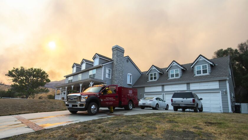 A brush engine from the AIG Wildfire Protection Unit staged at a home threatened by the Sand Fire on