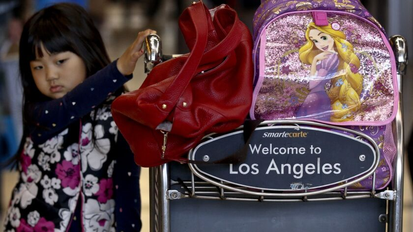 LOS ANGELES, CA., JANUARY 11, 2016: A young traveler waits with her family's luggage at the check-in