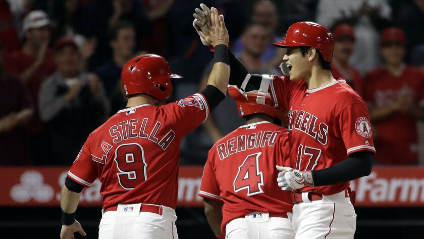 Los Angeles Angels' Shohei Ohtani, right, celebrates his three-run home run with teammate Tommy La S