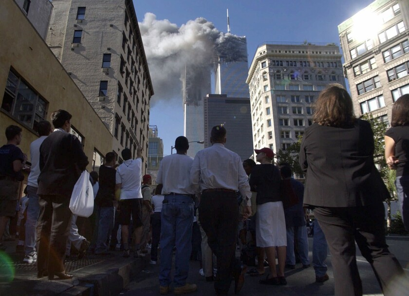 Pedestrians in lower Manhattan watch smoke billow from New York's World Trade Center on Tuesday, Sept. 11, 2001.