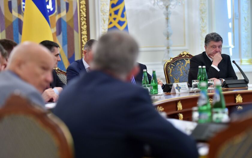 Ukrainian President Petro Poroshenko, right, chairs an emergency meeting of the country's National Security and Defense Council, called after Russia sent two armored columns across the border.