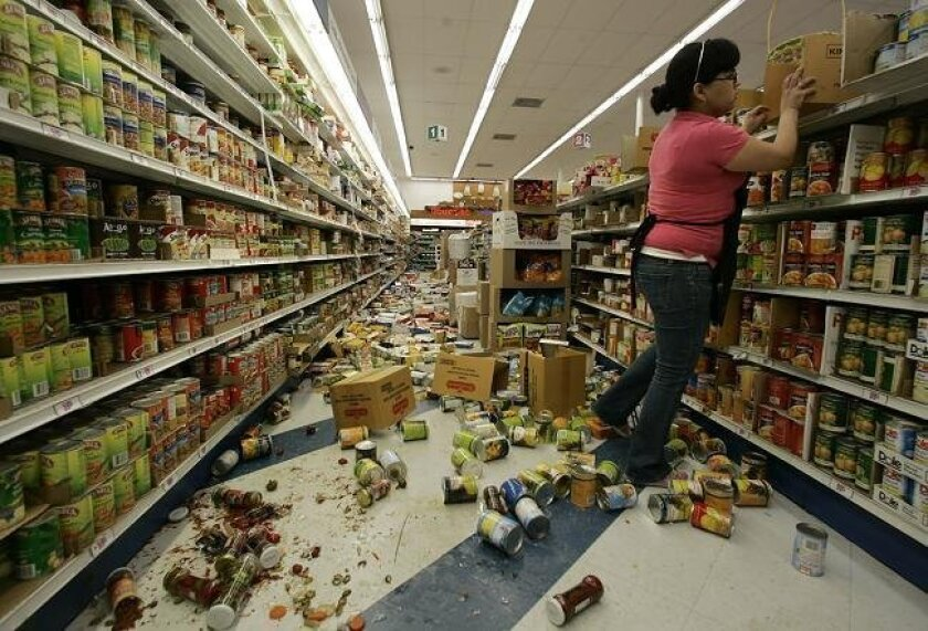 Brenda Mendez, store employee at the 99 Cent Store in Calexico, restocks items Monday morning. The damage done in Calexico from Sunday's earthquake was mainly along Second Street in the downtown area, where big glass windows were shattered.