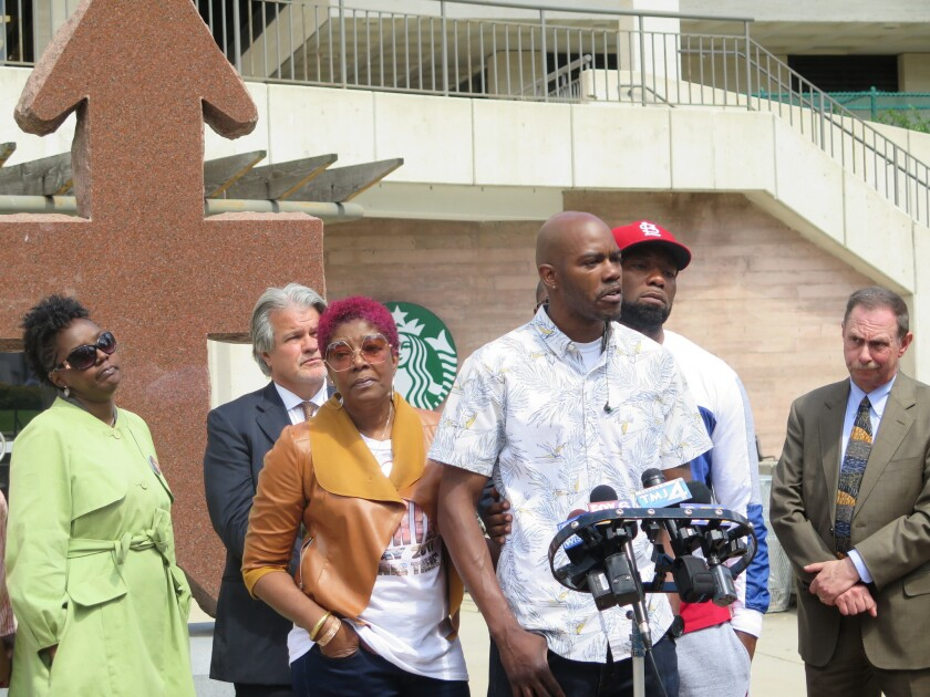 Nate Hamilton speaks during a news conference on May 31, 2017 in Milwaukee, while his mother, Maria Hamilton, left, looks on after the city approved a $2.3 million settlement for the 2014 fatal police shooting of his brother, Dontre Hamilton.