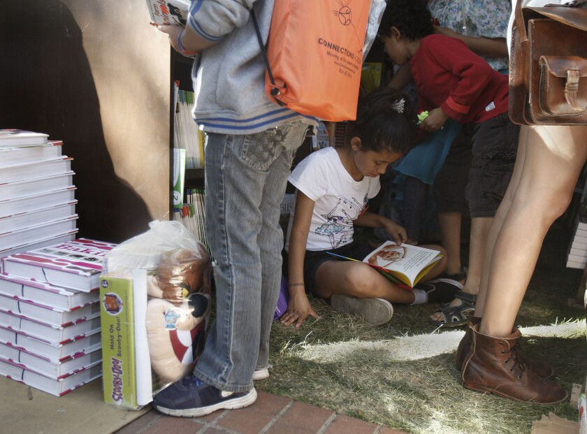 Alexis Nicholson, 9, reads a printed book at the 2013 Los Angeles Times Festival of Books.