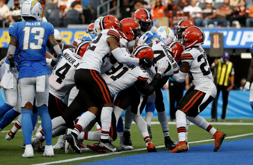 Chargers running back Austin Ekeler gets pulled into the end zone for the deciding score against the Browns.