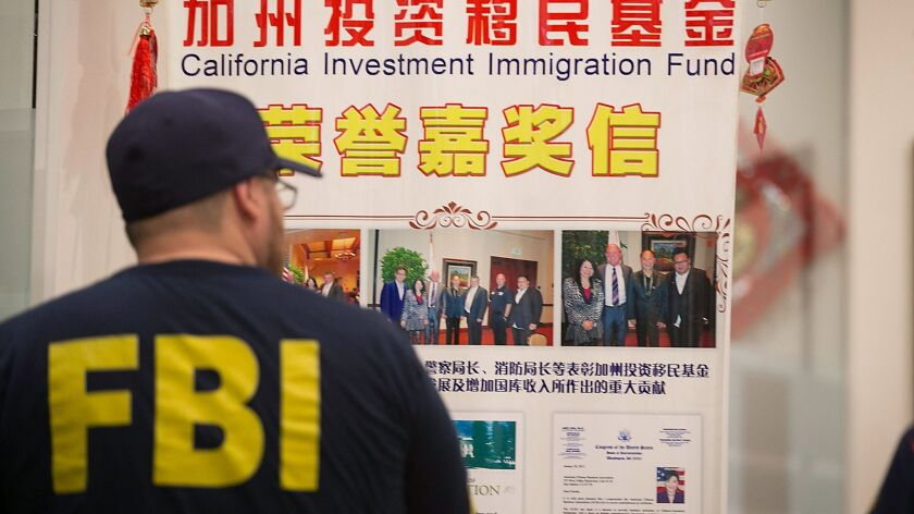 An FBI agent earlier this year searching the lobby of a San Gabriel Valley company that authorities alleged was used by an attorney and her father to run an immigration fraud scheme that netted tens of millions of dollars.