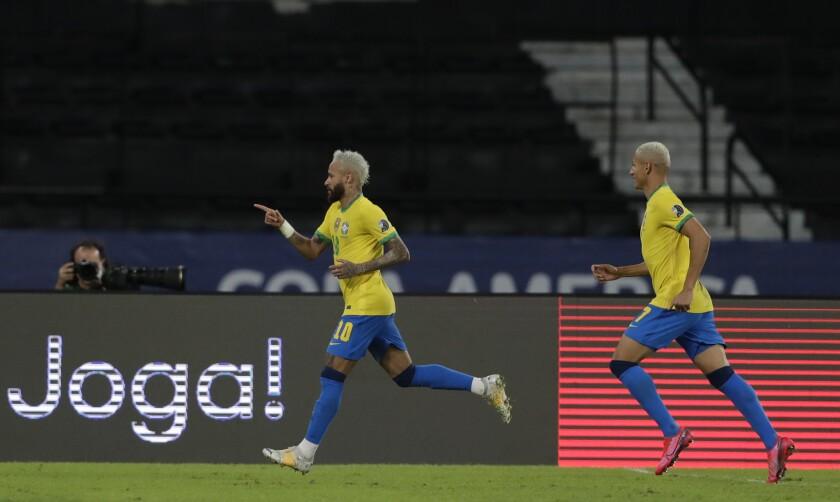 Brazil's Neymar, left, celebrates after scoring his side's 2nd goal during a Copa America soccer match against Peru at Nilton Santos stadium in Rio de Janeiro, Brazil, Thursday, June 17, 2021.(AP Photo/Silvia Izquierdo)