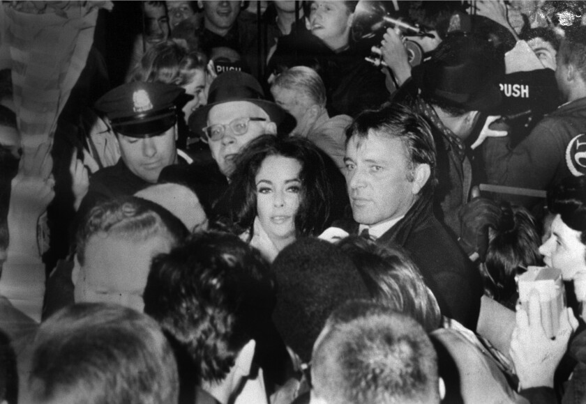 Elizabeth Taylor, center left, and her husband, Richard Burton, are mobbed by fans in Boston in March 1984.
