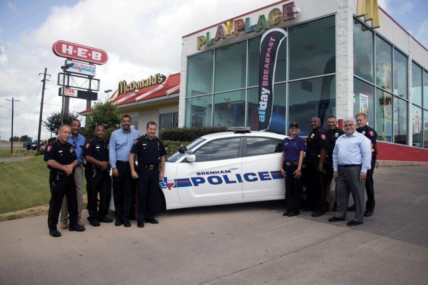 Members of the Brenham Police Department pose for a photo in front of a Texas McDonald's where officers were denied service. Owners of the restaurant fired an employee involved in the incident.