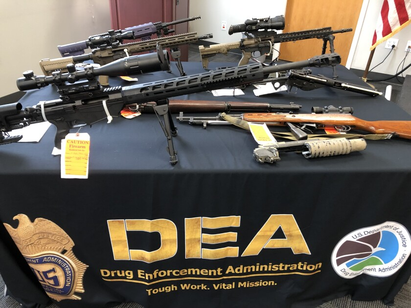 Some of 90 guns seized from a methamphetamine distribution network, on display at DEA San Diego on June 29, 2021.