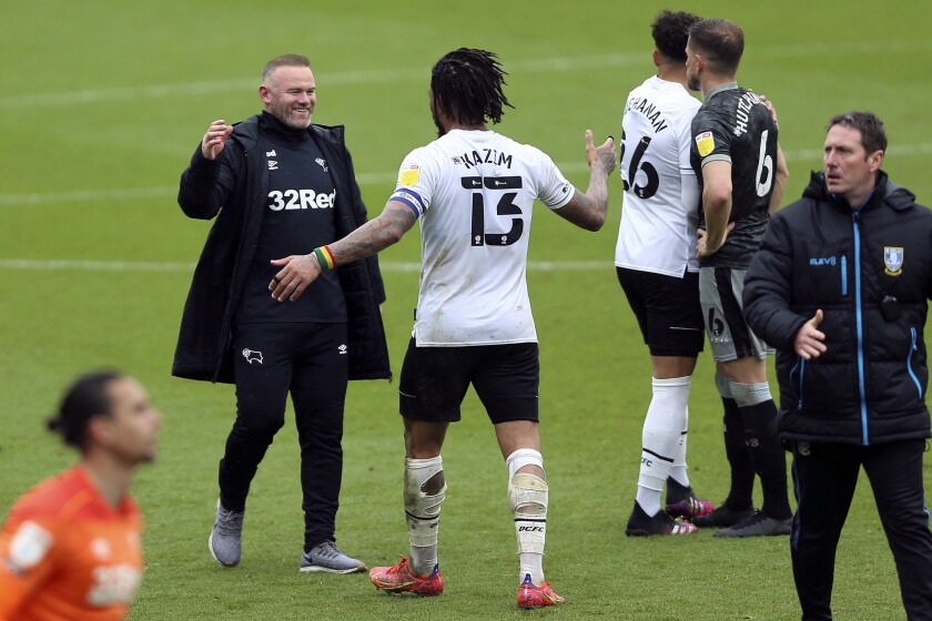 Derby County manager Wayne Rooney, left, celebrates with Colin Kazim-Richards (13) after a Sky Bet Championship soccer match at Pride Park, Saturday, May 8, 2021, in Derby, England. Rooney has kept a relegation off his resumé after his team came back to earn a vital point against Sheffield Wednesday in a season-ending 3-3 draw to stay in the English second division next season. (Nigel French/PA via AP)
