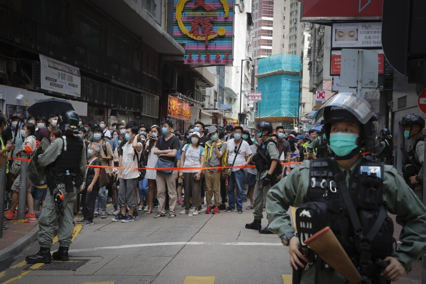 Hong Kong police place a perimeter line in Causeway Bay on July 1 before protesters begin their annual handover march.