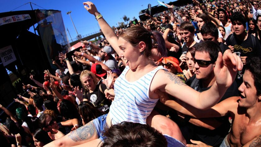 A fan crowd-surfs at the 2015 Vans Warped Tour stop at San Diego's Qualcomm Stadium.