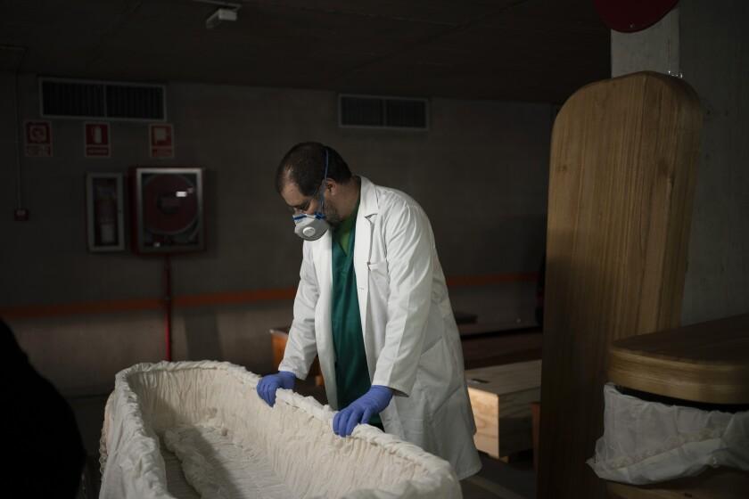 Mortician Jordi Fernandez prepares a coffin in Barcelona.
