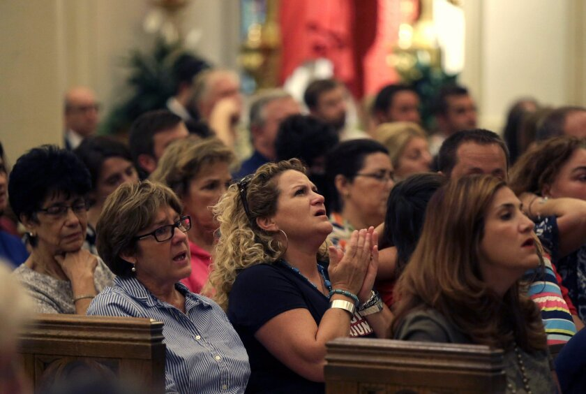 """Parishioners sing a hymn during a prayer service for the victims of The Grand 16 theater shooting at the Cathedral of St. John the Evangelist, in Lafayette, La., Sunday, July 26, 2015. John Russell Houser stood up about 20 minutes into Thursday night's showing of """"Trainwreck"""" and fired on the audience with a semi-automatic handgun. (AP Photo/Gerald Herbert)"""