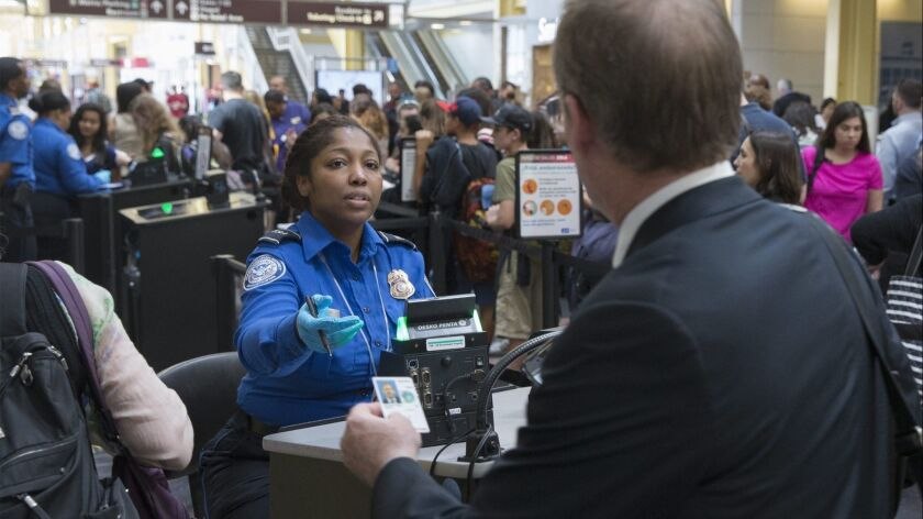 A Transportation Security Administration officer inspects a traveler's documents at Ronald Reagan Washington National Airport in Arlington, Va., in June 2016.