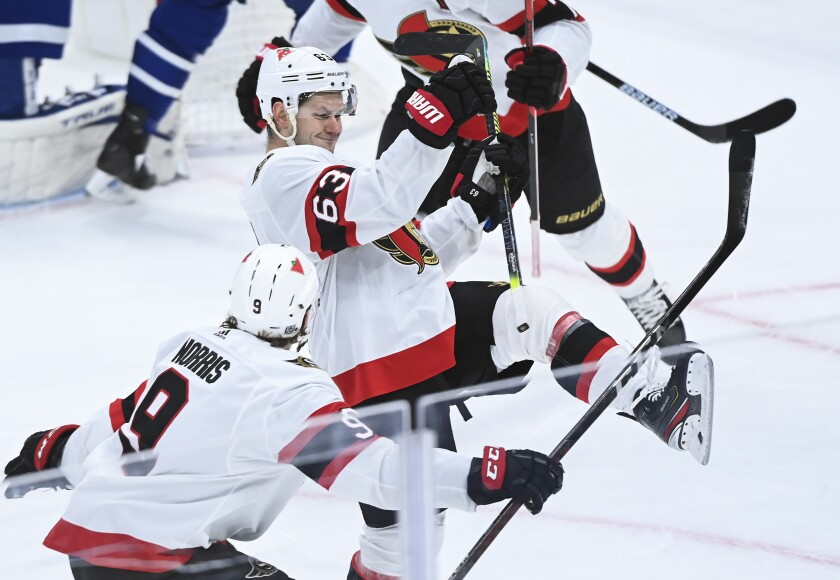Ottawa Senators right wing Evgenii Dadonov (63) scores the game tying goal against the Toronto Maple Leafs during the third period of an NHL hockey game, Monday, Feb. 15, 2021 in Toronto. (Nathan Denette/The Canadian Press via AP)